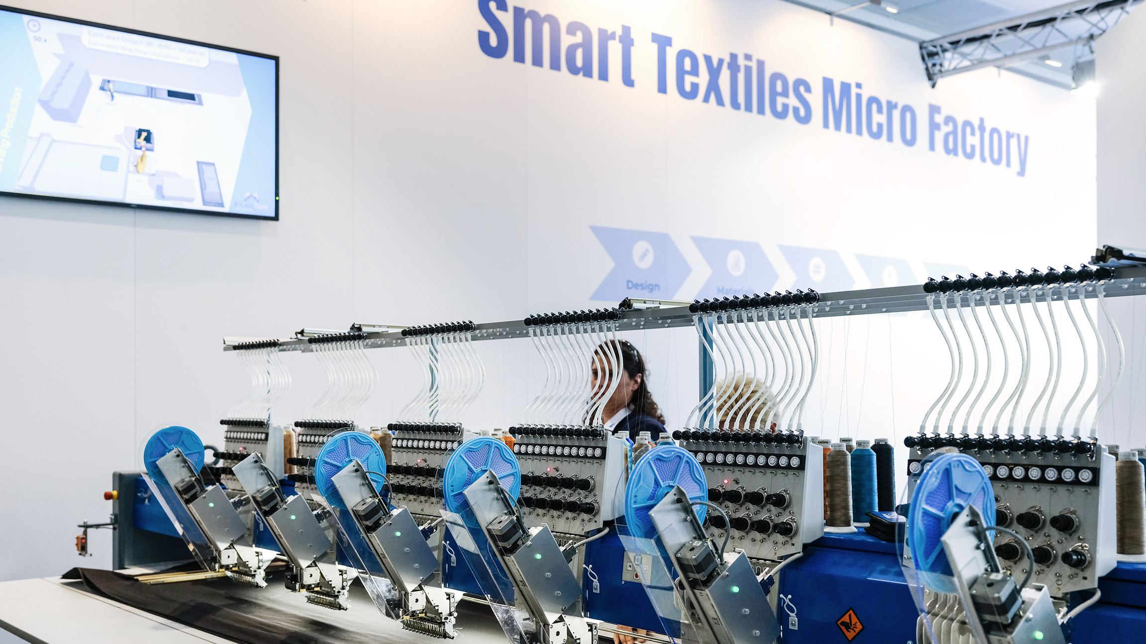 Visitors are talking to an exhibitor in the Digital Textile Micro Factory